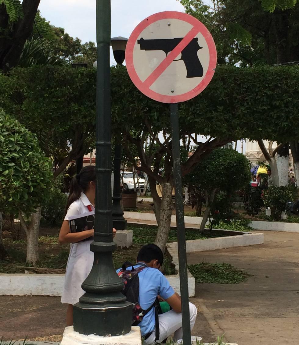 Señal de prohibido llevar armas en el parque de la catedral de Santa Ana.
