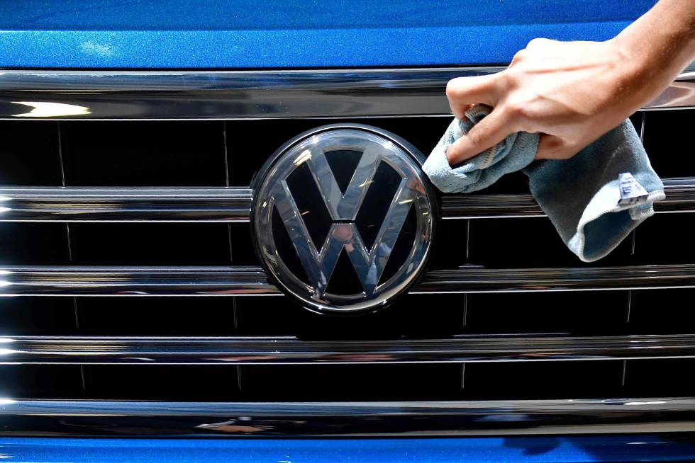 A staff member cleans the logo of a SUV VW Touareg on display ahead of the annual general meeting of German carmaker Volkswagen, in Berlin on May 3, 2018.  AFP PHOTO  Tobias SCHWARZ