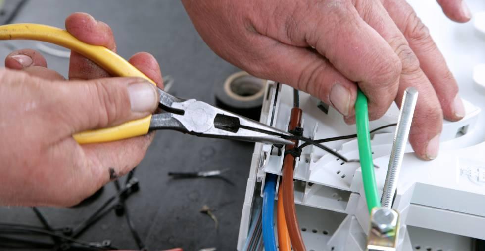 Un técnico manipula una instalación de fibra óptica.