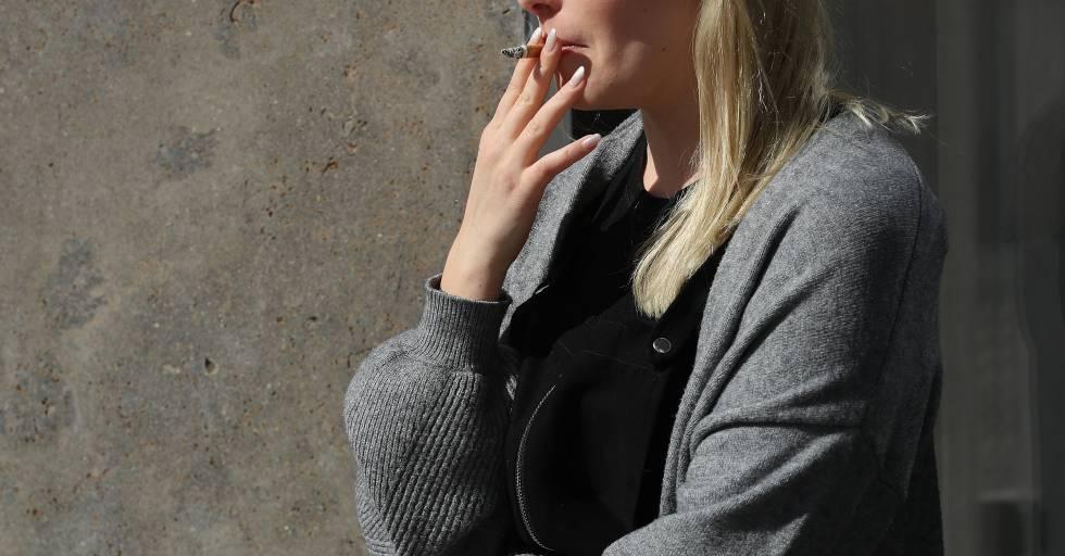 Una mujer fumando durante una pausa en el trabajo.