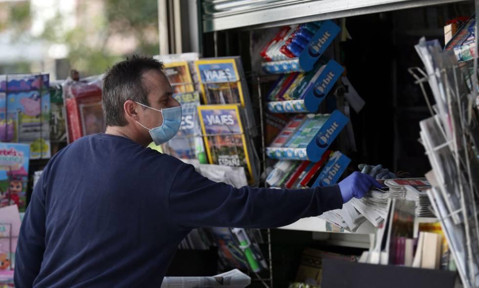 Un lector protegido con mascarilla compra periódicos este domingo en Bilbao