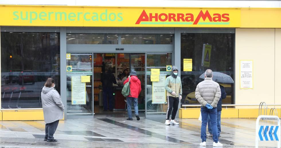 Varias personas esperan para poder entrar a comprar en un supermercado de Madrid en plena crisis sanitaria por coronavirus.