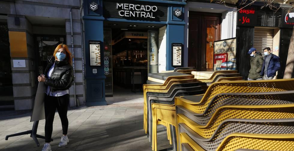 Camareros limpiando y poniendo las mesas en las terrazas de los bares a primera hora de las mañana en Granada.rn